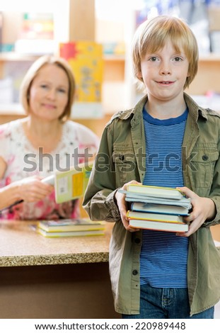 Portrait of happy schoolboy checking out books from library with librarian in background - stock photo