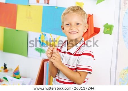Portrait of happy schoolboy with a paper crane - stock photo