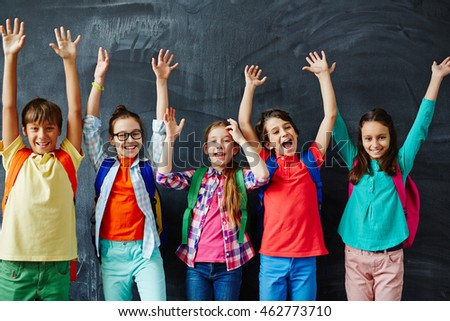 Portrait of happy schoolchildren standing with hands raised