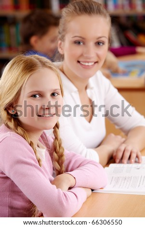 Portrait of happy schoolgirl and her teacher at background in library - stock photo