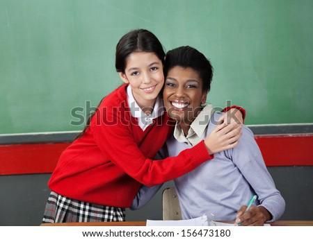 Portrait of happy schoolgirl hugging professor at desk in classroom - stock photo