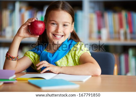 Portrait of happy schoolgirl with big red apple looking at camera in library - stock photo