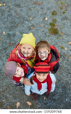 Portrait of happy schoolkids looking at camera outdoors - stock photo