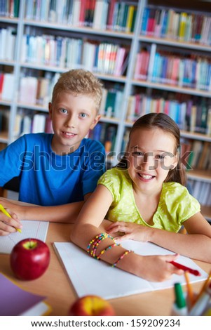 Portrait of happy schoolkids looking at camera while sitting in library - stock photo