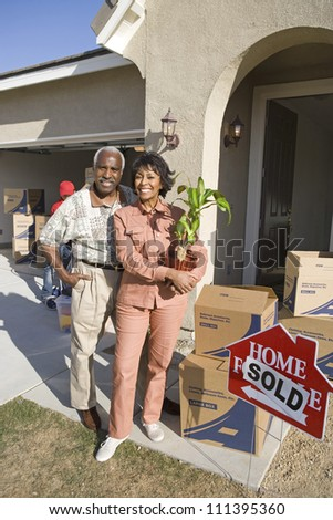 Portrait of happy senior African American couple moving to their new house - stock photo