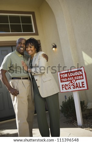 Portrait of happy senior African American couple standing in front of new house - stock photo