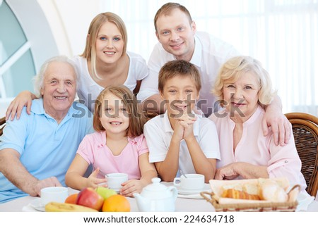 Portrait of happy senior and young couples and their children sitting by dinner table - stock photo