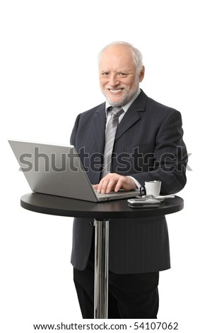 Portrait of happy senior businessman using laptop on coffee table, laughing, cutout.