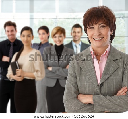 Portrait of happy senior businesswoman and her business team. - stock photo