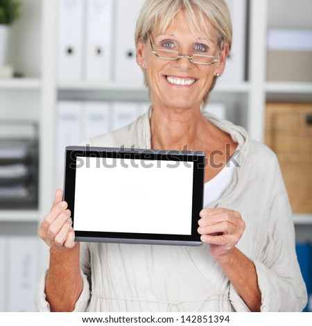 Portrait of happy senior businesswoman displaying digital tablet in office - stock photo