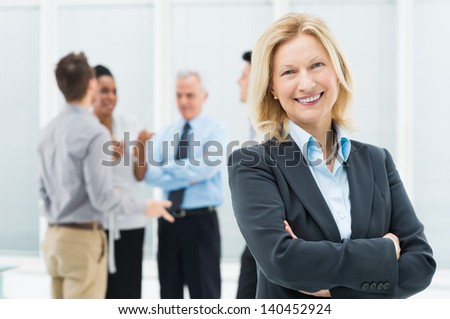 Portrait Of Happy Senior Businesswoman In Office With Her Colleagues - stock photo