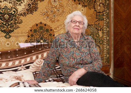 Portrait of happy senior caucasian woman in glasses about ninety years old sitting on bed in her bed room - stock photo