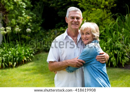 Portrait of happy senior couple embracing in back yard - stock photo