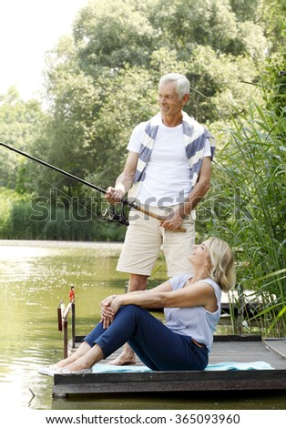 Portrait of happy senior couple fishing at lakeshore. Old man holding in his hand fishing rod while beautiful elderly woman sitting at pier and smiling.