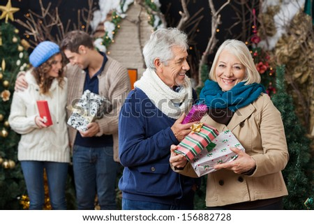 Portrait of happy senior couple holding Christmas presents with children standing in background at store - stock photo