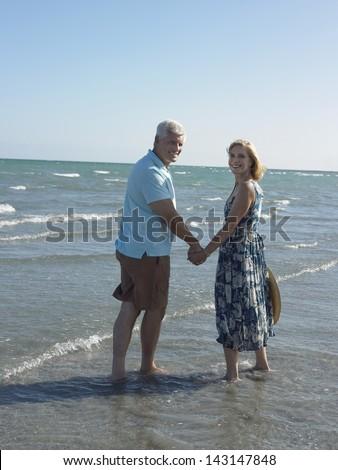Portrait of happy senior couple holding hands on tropical beach - stock photo