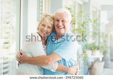 Portrait of happy senior couple hugging at home - stock photo