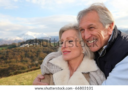 Portrait of happy senior couple in countryside - stock photo