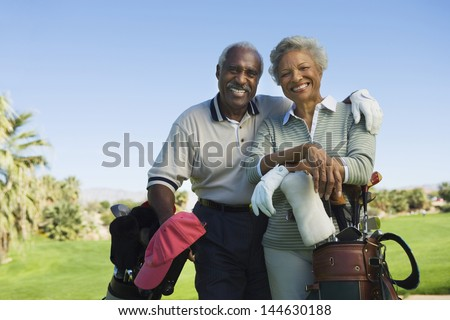 Portrait of happy senior couple in golf course smiling - stock photo
