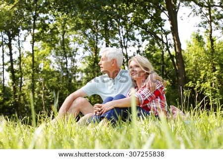 Portrait of happy senior couple in the nature. Senior man hugging mature woman while sitting in the grass and relaxing.