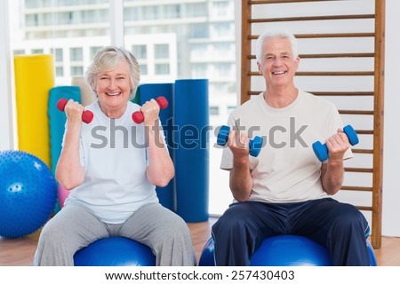 Portrait of happy senior couple lifting dumbbells while sitting on exercise ball at gym