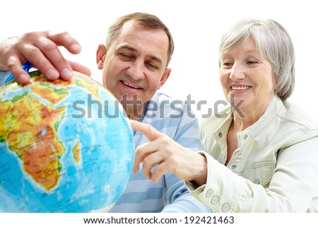 Portrait of happy senior couple looking at globe