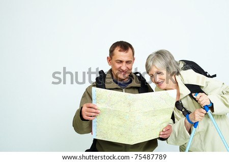 Portrait of happy senior couple looking at map on trip