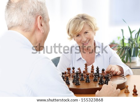 Portrait of happy senior couple playing chess together at home  - stock photo