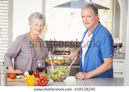 Portrait of happy senior couple preparing food while standing in kitchen - stock photo