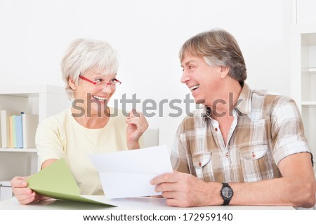 Portrait Of Happy Senior Couple Reading Letter Together - stock photo
