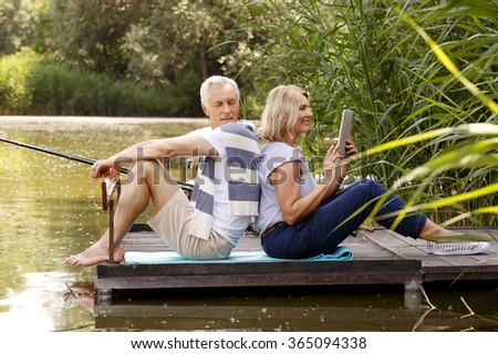 Portrait of happy senior couple relaxing at lakeshore. Old man fishing and elderly woman using digital tablet while sitting at pier.