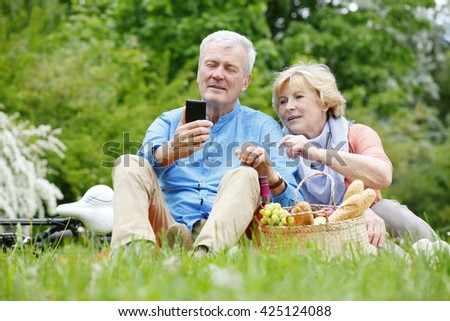 Portrait of happy senior couple seated on the grass and using mobile phone while relaxing outdoor. - stock photo