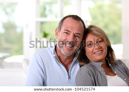 Portrait of happy senior couple sitting in sofa - stock photo