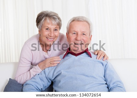 Portrait Of Happy Senior Couple Sitting On Couch - stock photo
