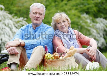 Portrait of happy senior couple sitting outdoor and relaxing.  - stock photo
