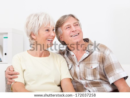 Portrait Of Happy Senior Couple Sitting Together Side By Side Looking Away - stock photo