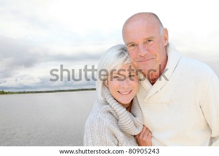 Portrait of happy senior couple standing by a lake