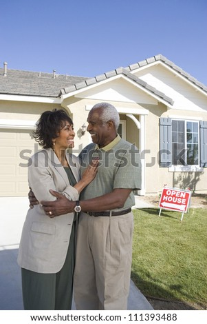 Portrait of happy senior couple standing in front of house for sale - stock photo
