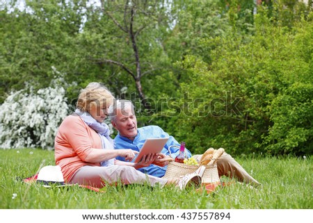 Portrait of happy senior couple using digital tablet while relaxing and picnic outdoors. - stock photo