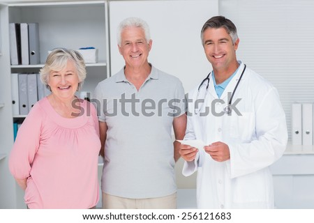 Portrait of happy senior couple with doctor standing in clinic