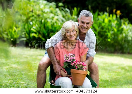 Portrait of happy senior couple with flower pots in yard - stock photo