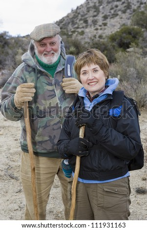 Portrait of happy senior couple with sticks hiking