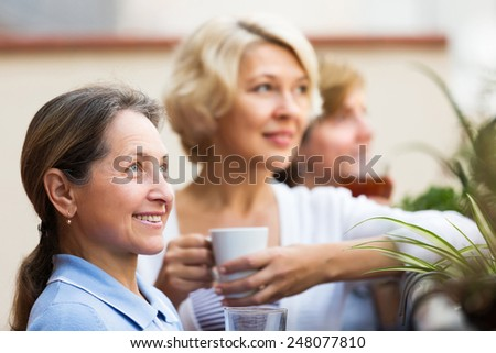 Portrait of happy senior female friends on summer terrace. Focus on brunette female   - stock photo