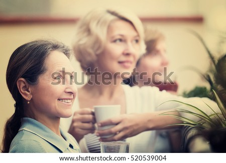 Portrait of happy senior female friends on summer terrace. Focus on brunette female