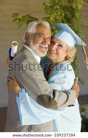 Portrait of happy senior female graduate embracing man - stock photo