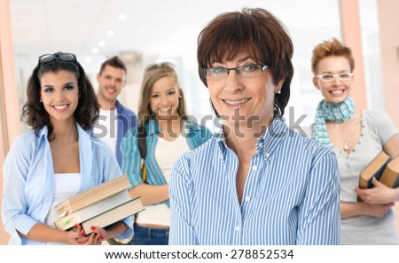 Portrait of happy senior female teacher with group of students in background.