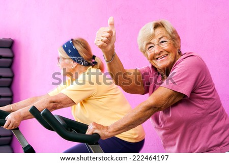 Portrait of happy Senior fitness woman doing thumbs up at spinning session in gym.