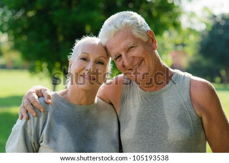 Portrait of happy senior husband and wife after fitness in city park - stock photo