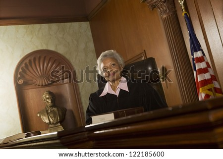 Portrait of happy senior judge sitting in courtroom - stock photo