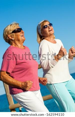 Portrait of happy senior ladies jogging together at seaside. - stock photo